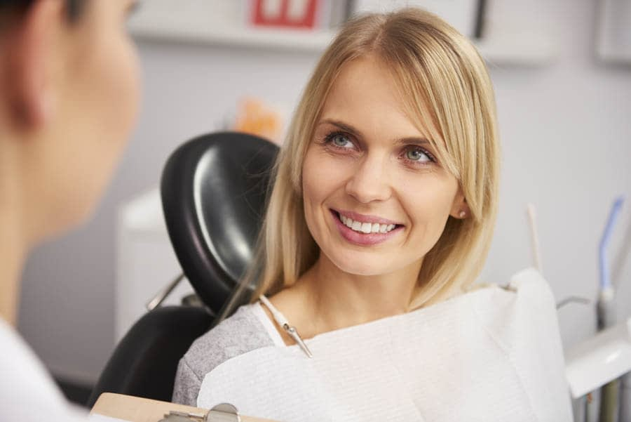 Pleased and smiling woman in dentist's clinic
