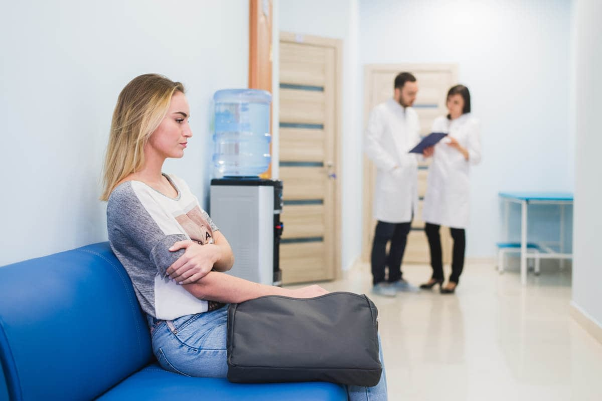 Young woman filling nervous sitting at hospital corridor waiting while two doctors talking on a backgroud