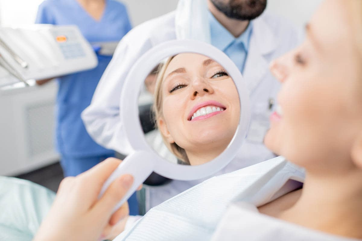Reflection in mirror of healthy smile of pretty young smiling female patient